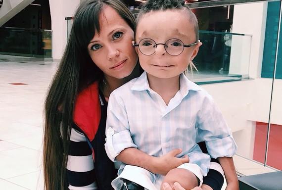 На фото мальчик Рустам на руках у приёмной мамы
