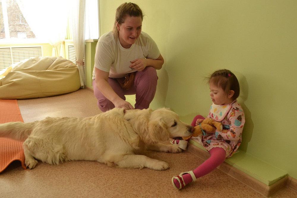 Собака породы золотистый ретривер и женщина с маленькой девочкой