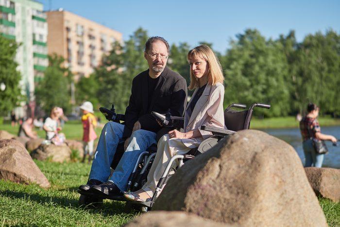 На фото мужчина и женщина в креслах-колясках в парке