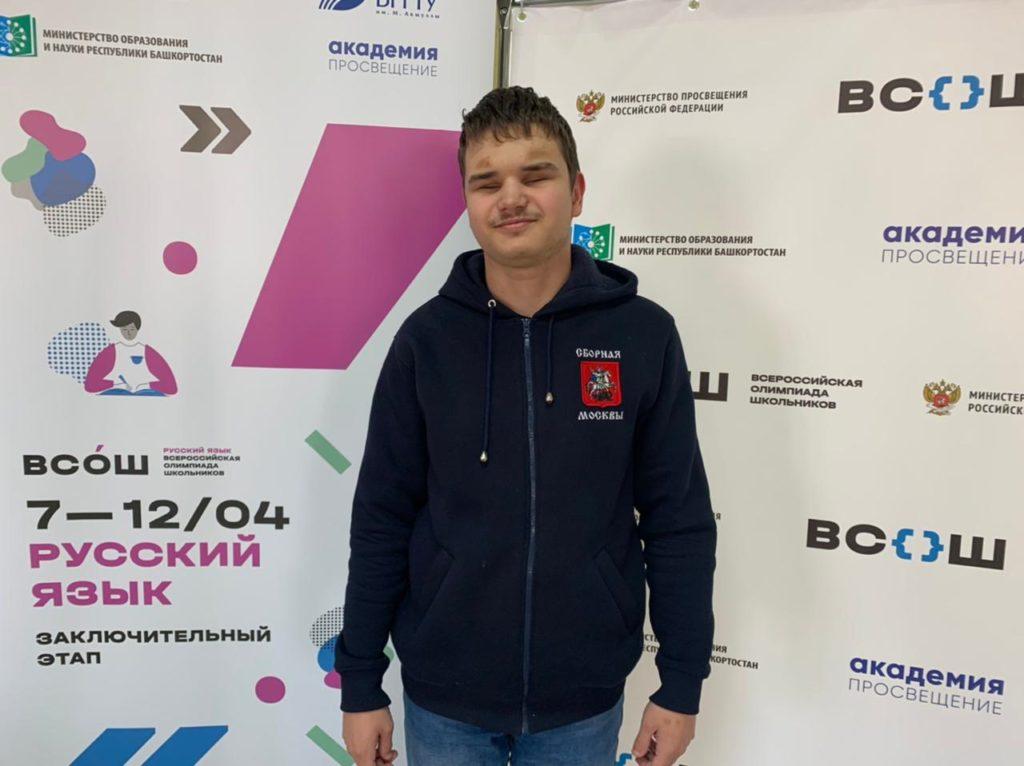 Андрей Якубой возле стенда Всероссийской олимпиады по русскому языку
